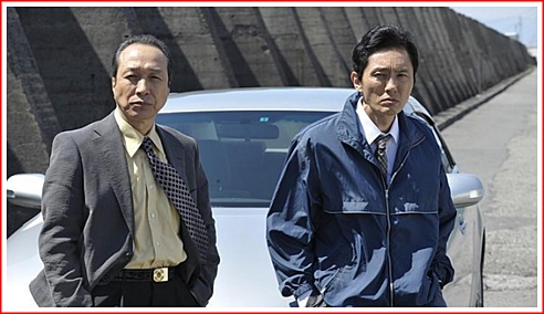 Kataoka (in the shirt and tie on the left) and his junior detective (in the windbreaker on the right) wait for Otomo to exit the prison