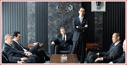 That's Kato seated facing us, and Ishihara standing with arms crossed, at a meeting of the Sanno crime family bosses.