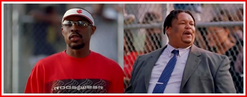 Avon Barksdale in red tee is played by Wood Harris. Prop Joe, in the suit, is played by Robert Chew. Avon:  Why you wearing that suit? It's 85 fucking degrees out here and you trying to be Pat Riley Prop Joe: Look the part, be the part, motherfucker...
